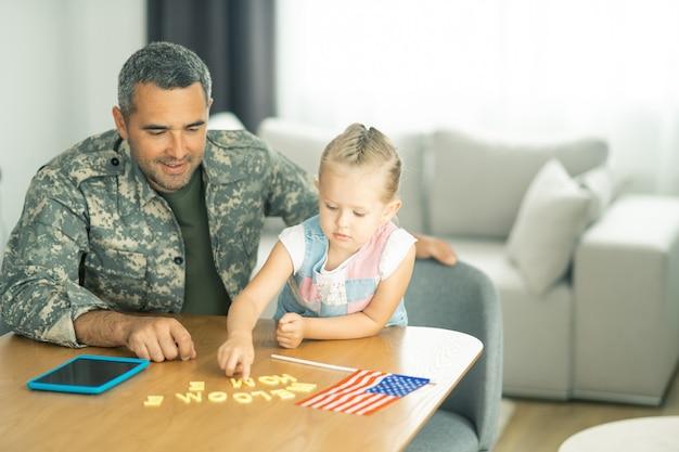 Tatuś w domu. śliczna blondynka wita tatusia w mundurze wojskowym w domu