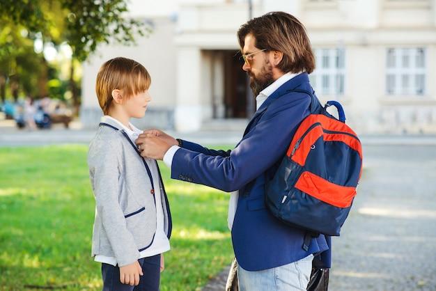 Tatuś wspiera syna za rozpoczęcie nauki w szkole.
