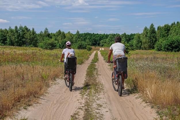 Tatusiowie jeżdżą ze swoimi dziećmi w fotelikach rowerowych po polnej drodze przez las