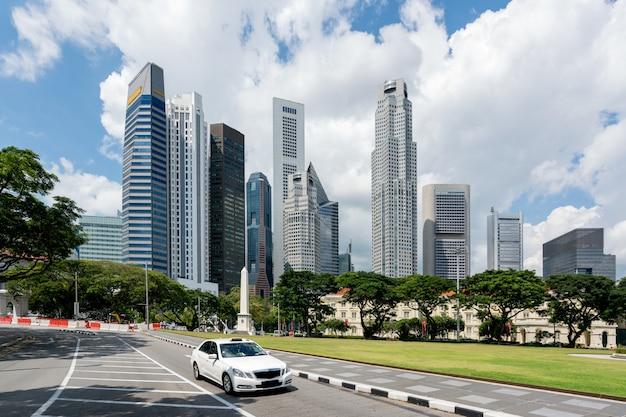 Taxi taksówki jeżdżenie w drodze w singapur śródmieściu z singapur drapaczami chmur buduje w tle. azja.