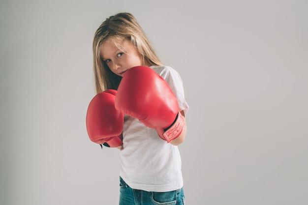 Tchórzliwa śmieszna młoda dziewczyna w czerwonych bokserskich rękawiczkach