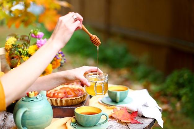 Tea party z czajnikiem, kubkami, szarlotką przy drewnianym stole w ogrodzie