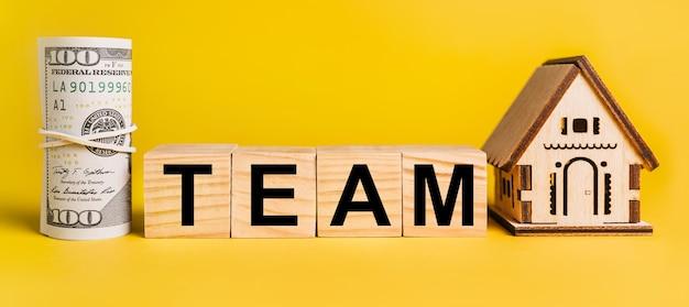 Team z miniaturowym modelem domu i pieniędzmi na żółtej powierzchni