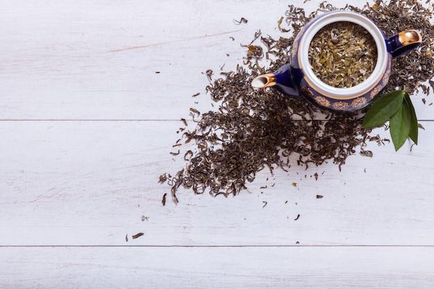 Teapot i wysuszeni herbaciani liście na białym drewnianym tle, odgórny widok