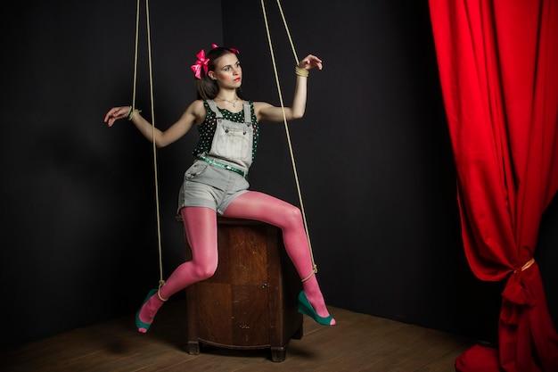 Teatr lalkowy. halloween marionetka kobieta na szafie z rękami związany pozowanie. kobieta na ciemnym tle. fotografia mody