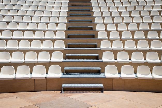 Teatr na świeżym powietrzu z naturalnym światłem dziennym; plastikowe rzędy siedzeń