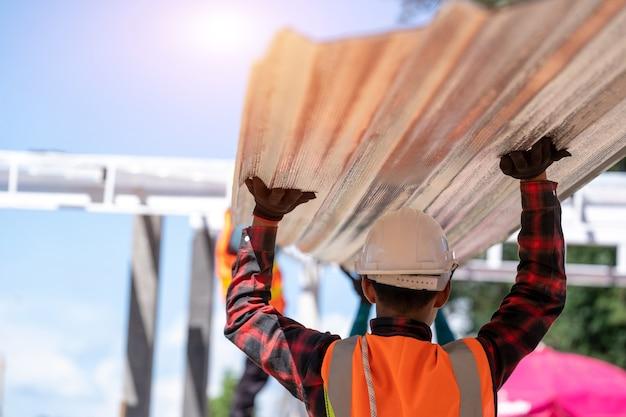 Technicy dekarzy pracują i instalują nową konstrukcję dachu na dachu domu, dach metalowy, elementy mocujące blachy faliste.