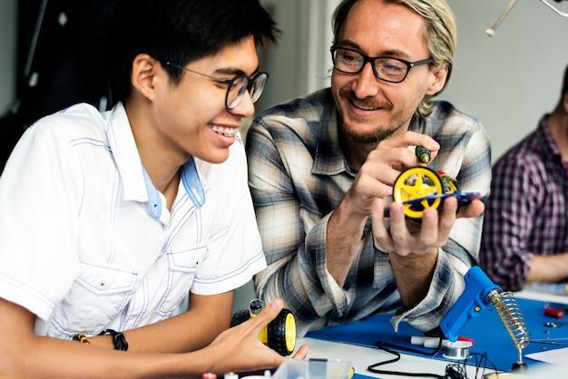 Technicy elektrotechniczni pracujący na częściach elektroniki robotów