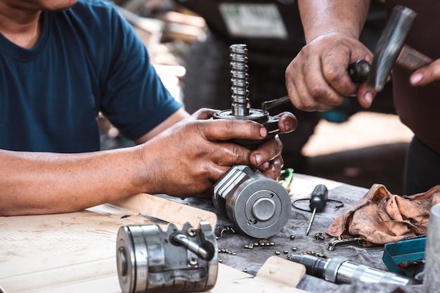 Technicy pomagają w montażu przekładni kierowniczej ze wspomaganiem samochodu.
