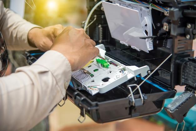 Technicy są szafą instalacyjną na kablu światłowodowym