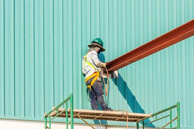 Technicy spawają stalową konstrukcję. obraz strony budowy w tle.