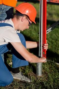 Technicy zajmują się montażem śrubowych pali śrubowych do paneli słonecznych.