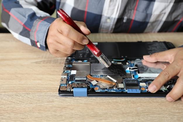 Technik człowiek za pomocą szczotki do odkurzania do czyszczenia komputera przenośnego