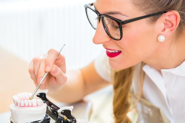 Technik dentystyczny produkujący protezę