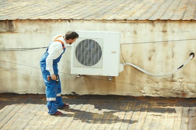Technik hvac pracujący nad częścią kondensatora do agregatu skraplającego. pracownik lub mechanik w mundurze naprawiający i regulujący system klimatyzacji, diagnozujący i szukający problemów technicznych.