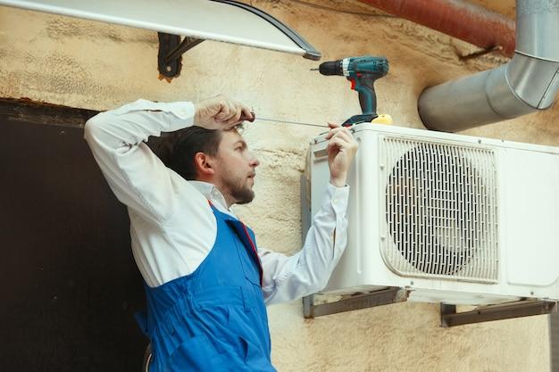 Technik hvac pracujący nad częścią kondensatora do agregatu skraplającego