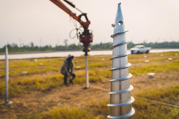 Technik instalujący śrubę uziemiającą do montażu konstrukcji panelu słonecznego na farmie słonecznej
