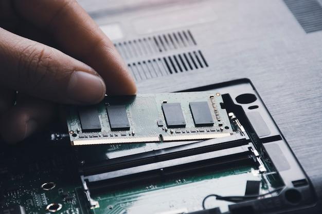 Technik instaluje nową pamięć ram o dostępie swobodnym do gniazda pamięci na płycie głównej laptopa