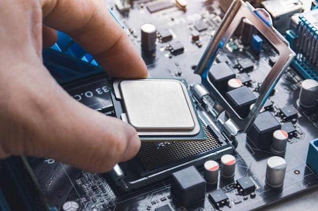 Technik instaluje układ procesora procesora w gnieździe na płycie głównej komputera;