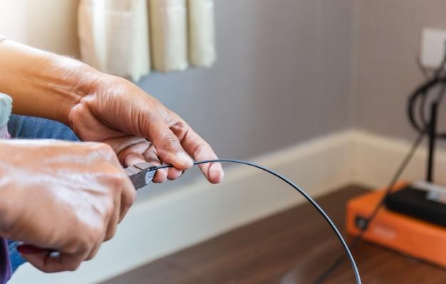 Technik internetowy przecina kable światłowodowe instalacyjne, domowa sieć it
