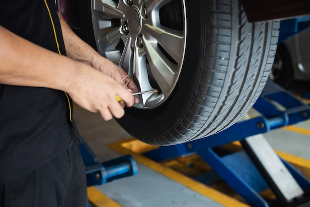 Technik jest napompować oponę samochodową, serwis konserwacji samochodu bezpieczeństwo transportu