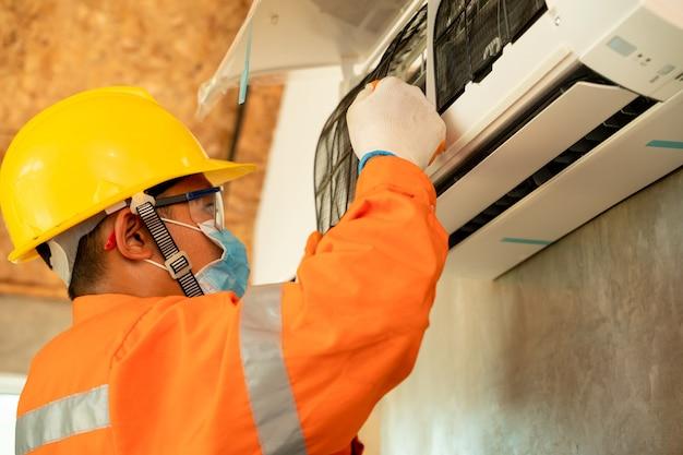 Technik klimatyzacji, elektryk instaluje klimatyzator w pomieszczeniu.