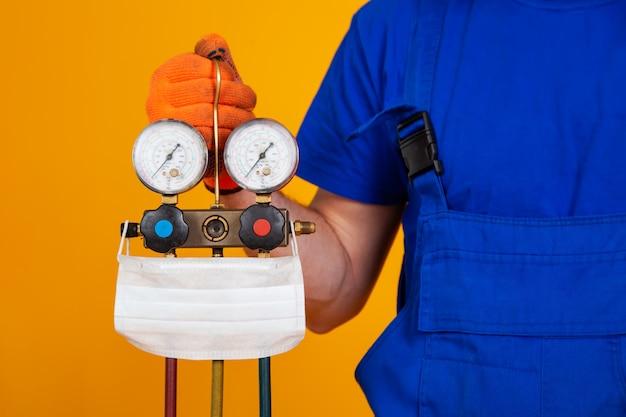 Technik klimatyzacji trzyma w dłoni manometry do tankowania klimatyzatorów. medyczna osłona twarzy na urządzeniu pomiarowym do napełniania klimatyzatorów