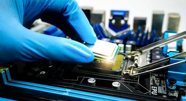 Technik komputerowy mocuje procesor do płyty głównej za pomocą rękawiczek zbliżenie