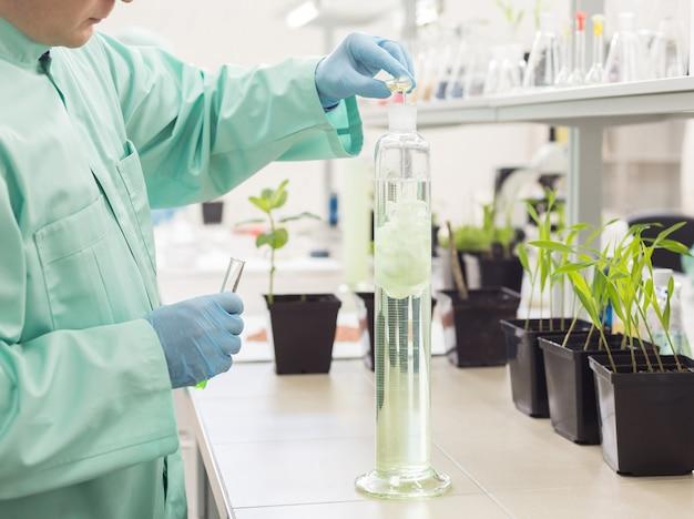 Technik laboratoryjny nalewa płyn do wysokiej kolby na tle laboratorium.