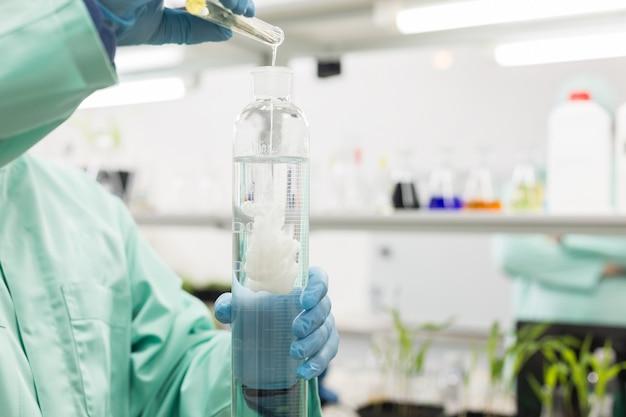 Technik laboratoryjny nalewa płyn do wysokiej kolby w laboratorium.