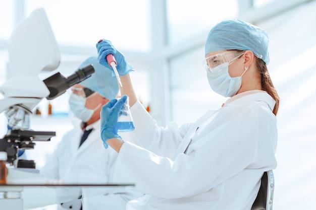 Technik laboratoryjny testujący ciecz w kolbie laboratoryjnej