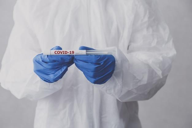 Technik laboratoryjny trzyma probówkę na koronawirusa do testu covid-19.