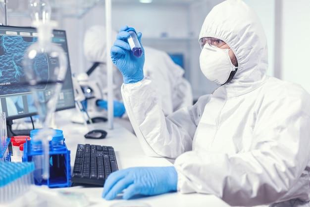 Technik laboratoryjny ubrany w kombinezon ochronny jako środek ostrożności, patrząc na probówkę