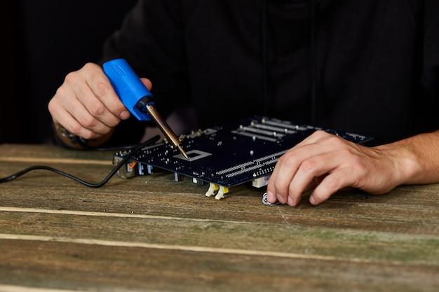 Technik lub inżynier koncentruje się na naprawie płytki drukowanej za pomocą lutownicy.