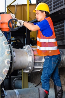Technik lub inżynier pracujący przy zaworze w sprzęcie technicznym budynku lub na terenie przemysłowym w fabryce lub zakładzie użyteczności publicznej
