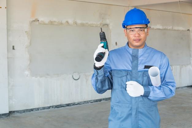 Technik lub mechanik nosi niebieski kask ochronny i strój ochronny