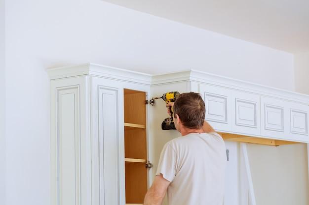 Technik mężczyzna instaluje szafki kuchenne