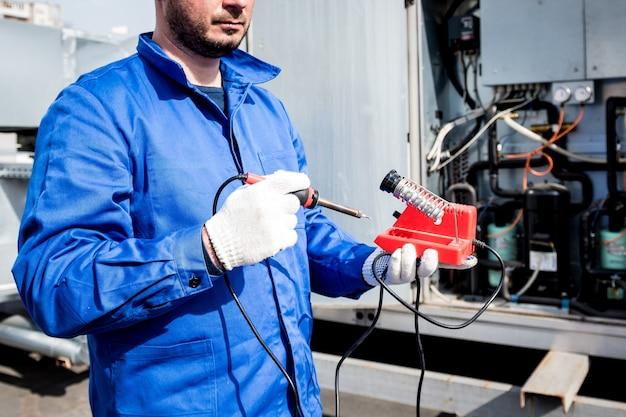 Technik naprawia elektroniczne czujniki temperatury lutownicą elektroniczną electronic