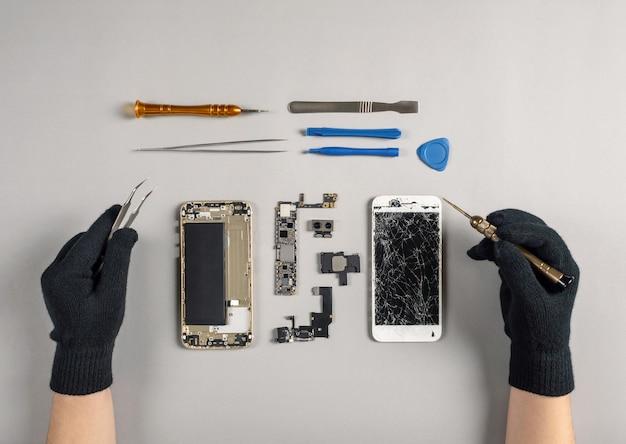Technik naprawia łamającego smartphone na biurku
