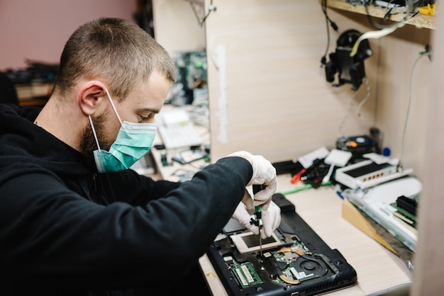 Technik naprawia laptop w laboratorium. koncepcja naprawy komputera, elektroniki, aktualizacji, technologii. koronawirus. obsługuje działanie, będący ubranym maskę ochronną w warsztacie.