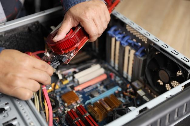Technik naprawia lub aktualizuje kartę vga na komputerze