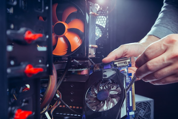 Technik naprawiający komputer, proces wymiany komponentów na płycie głównej.