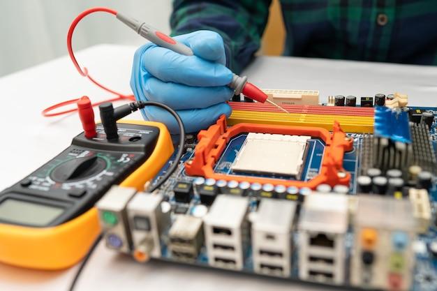 Technik naprawiający wnętrze dysku twardego lutownicą.