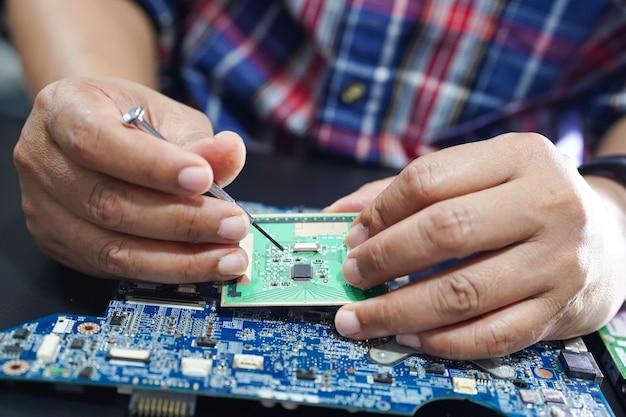 Technik naprawiający wnętrze dysku twardego lutownicą