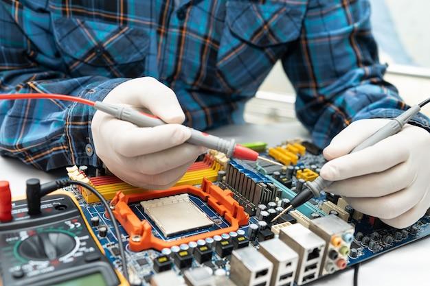 Technik naprawiający wnętrze dysku twardego za pomocą lutownicy. układ scalony. pojęcie danych, sprzętu, technika i technologii.