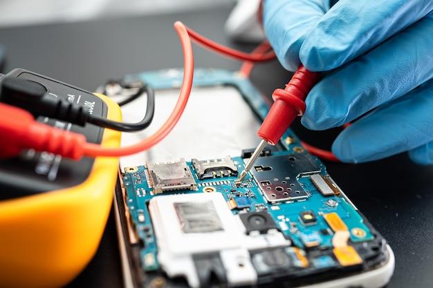 Technik naprawiający wnętrze telefonu komórkowego za pomocą lutownicy. układ scalony. pojęcie danych, sprzętu, technologii.