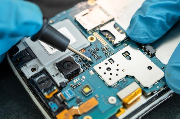 Technik naprawiający wnętrze telefonu komórkowego za pomocą lutownicy
