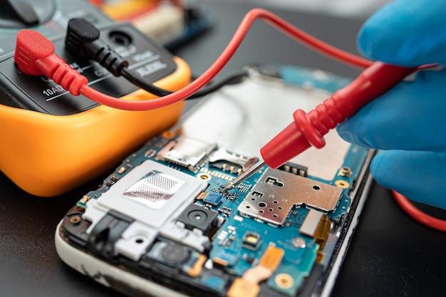 Technik naprawiający wnętrze telefonu za pomocą lutownicy. układ scalony. pojęcie danych, sprzętu, technologii.