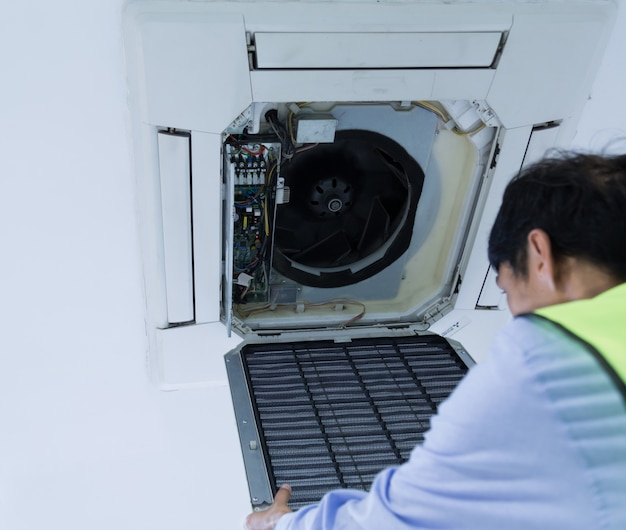 Technik naprawy klimatyzatora na ścianie.
