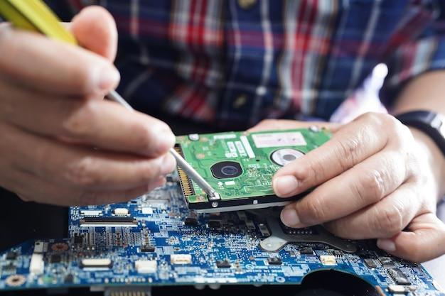 Technik naprawy wnętrza dysku twardego za pomocą lutownicy.